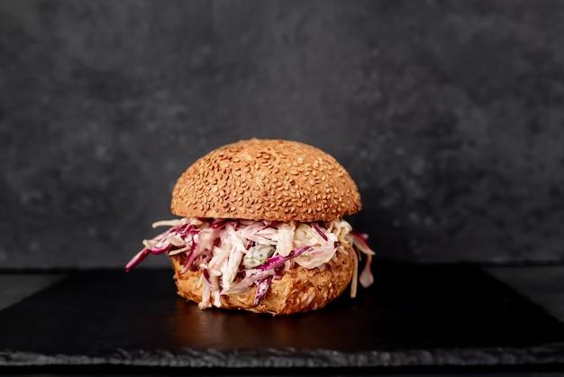 Hambúrguer de rabada de boi e repolho em mesa de pedra