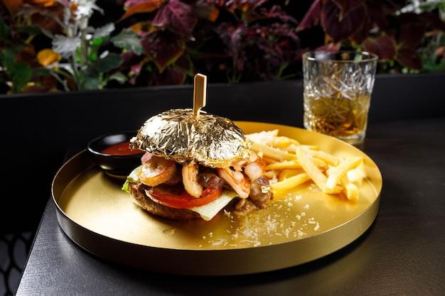 Hambúrguer de salmão e camarão, maionese no pão de baixo, patty de camarão salmão à milanesa e molho tártaro com camarão fresco no fundo de tábuas de madeira cinza