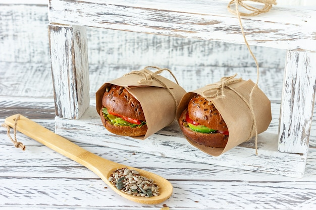 Hambúrguer de salmão saudável com abacate e tomate servido em papel artesanal em fundo de madeira.