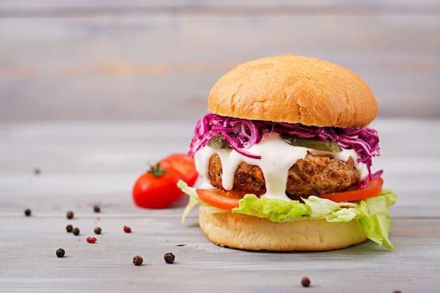 Hambúrguer de sanduíche com hambúrgueres suculentos, tomate e repolho roxo
