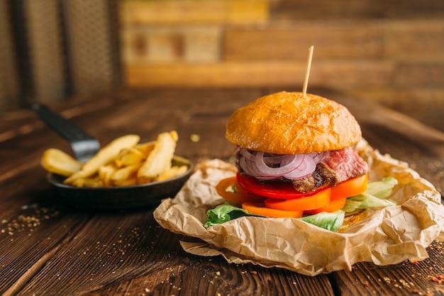 Hambúrguer de suco com bife fresco na mesa de madeira closeup, ninguém. hambúrguer com bife, preparação de alimentos, culinária