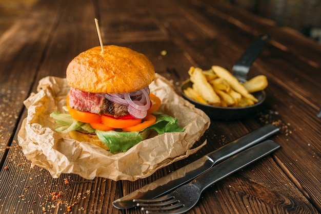 Hambúrguer de suco com bife na mesa de madeira closeup