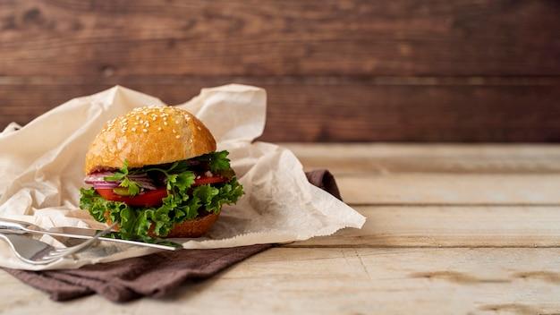 Hambúrguer de vista frontal com fundo de madeira