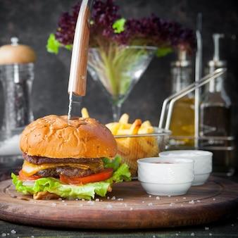 Hambúrguer de vista lateral com batatas fritas e tigela para molho e faca na bandeja de comida de madeira no restaurante