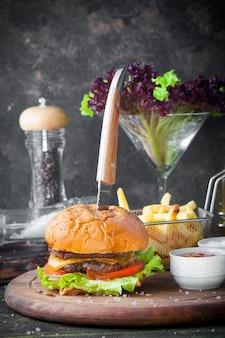 Hambúrguer de vista lateral com faca e tigela de molho e batatas fritas na bandeja de comida de madeira no restaurante