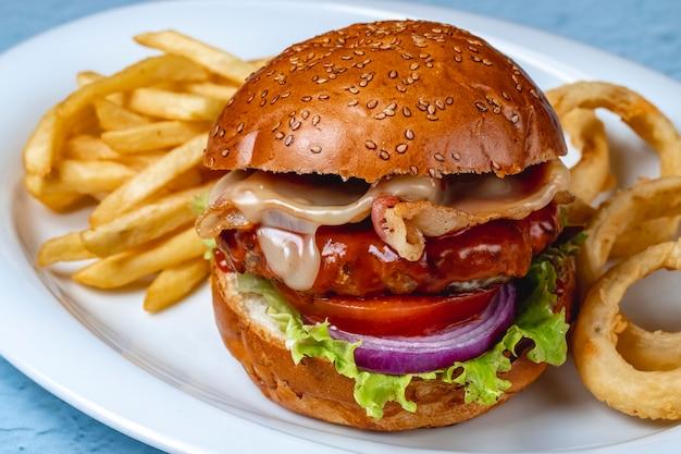 Hambúrguer de vista lateral com rissol de carne grelhada bacon queijo frito alface cebola vermelha tomate e batata frita em um prato