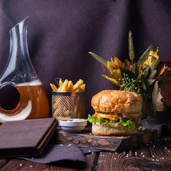 Hambúrguer de vista lateral e batatas fritas em madeira e fundo preto com decorações