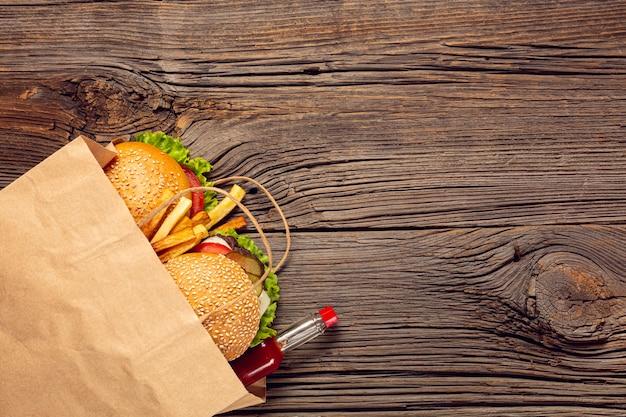 Hambúrguer de vista superior com batatas fritas em um saco