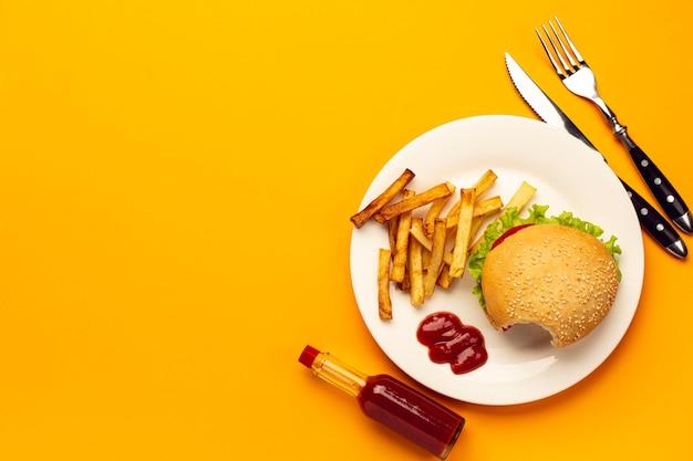 Hambúrguer de vista superior com batatas fritas num prato