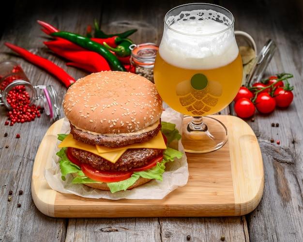 Hambúrguer de vitela com queijo e cerveja na mesa de madeira