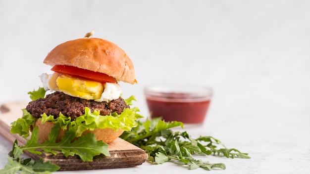 Hambúrguer delicioso com copo de ketchup turva