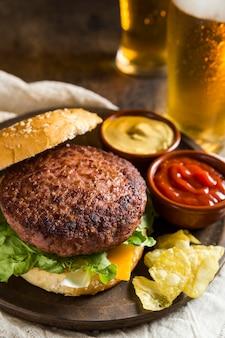 Hambúrguer delicioso com copos de cerveja e mostarda