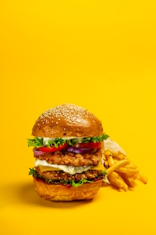 Hambúrguer duplo grande com costeleta de frango à milanesa e batatas fritas