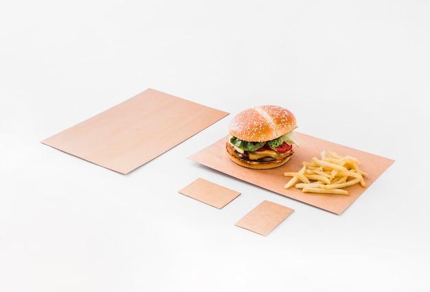 Hambúrguer e batatas fritas em papel pardo sobre fundo branco