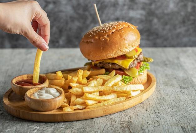Hambúrguer e batatas fritas em uma bandeja de madeira com molhos