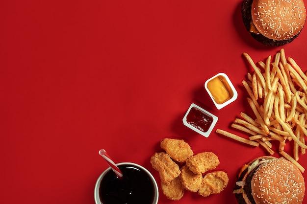 Hambúrguer e batatas fritas. hambúrguer e batatas fritas em caixa de papel vermelha. fast food em fundo vermelho. hambúrguer com molho de tomate. vista de cima, plana com copyspace