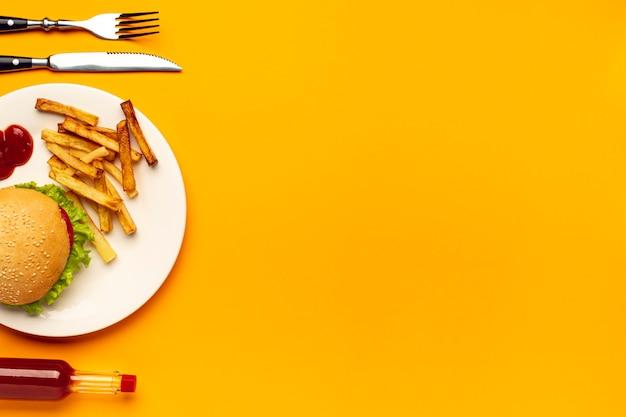 Hambúrguer e batatas fritas na chapa com espaço de cópia