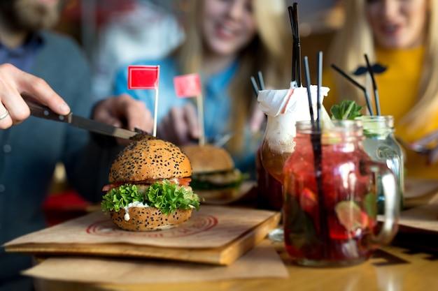 Hambúrguer e coquetel em uma mesa de madeira em um close-up do restaurante.