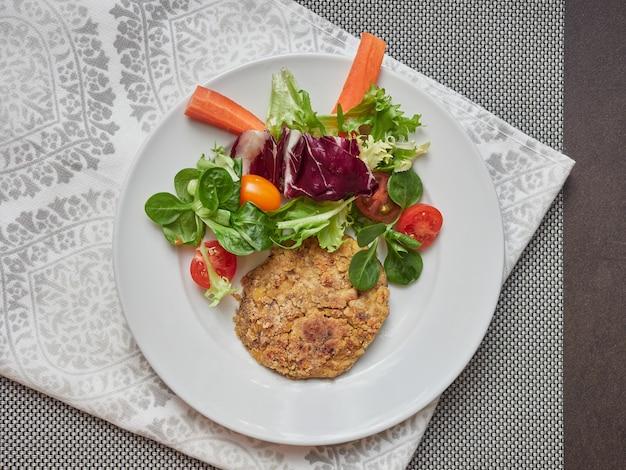 Hambúrguer e salada vegetariana de grão de bico em um prato branco sobre uma toalha de mesa e guardanapo cinza, vista de cima