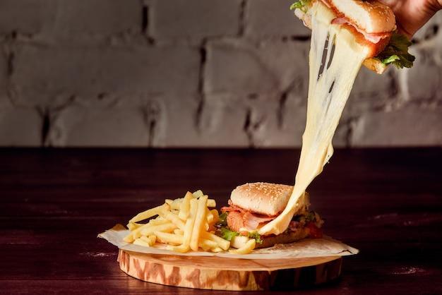 Hambúrguer em corte com costeleta, queijo derretido, bacon, alface, tomate e batata no pergaminho em uma bandeja de madeira sobre uma mesa de madeira.