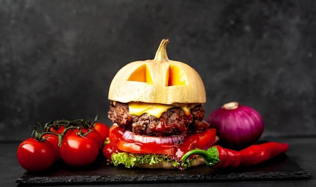 Hambúrguer em forma de abóbora para o feriado de halloween na parede de pedra