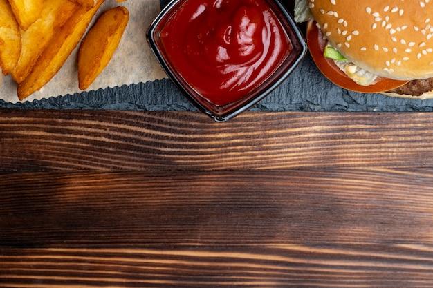 Hambúrguer em papel com batatas em um rústico e ketchup e na ardósia, placa preta e fundo de madeira queimada. vista do topo. copie o espaço.
