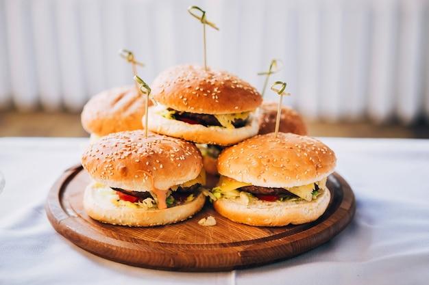 Hambúrguer em uma tábua de madeira redonda. pão com gergelim. pilha de hambúrgueres em um branco