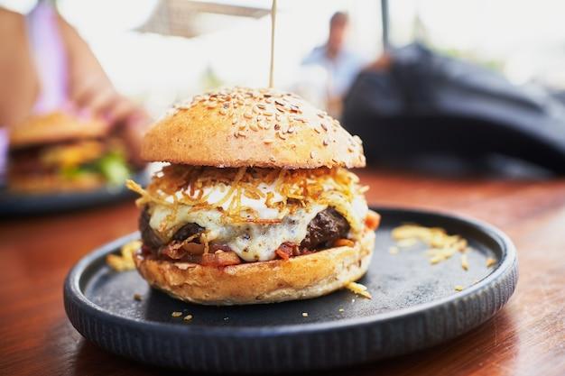 Hambúrguer enorme e gostoso com queijo, bacon, batatas fritas, molho de trufas e cebola servido em prato preto