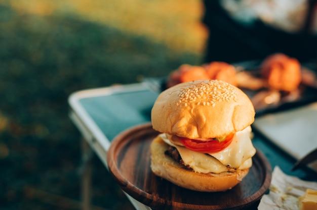 Hambúrguer enquanto acampa em um acampamento selvagem, acampamento cozinhando na margem do lago. Foto Premium