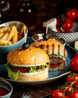 Hambúrguer fatiado com azeitona e batatas fritas