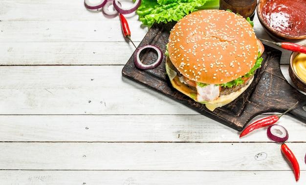 Hambúrguer fresco de carne com queijo e vegetais em um fundo branco de madeira