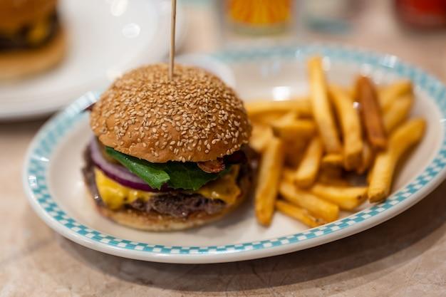 Hambúrguer fresco e batatas fritas na mesa