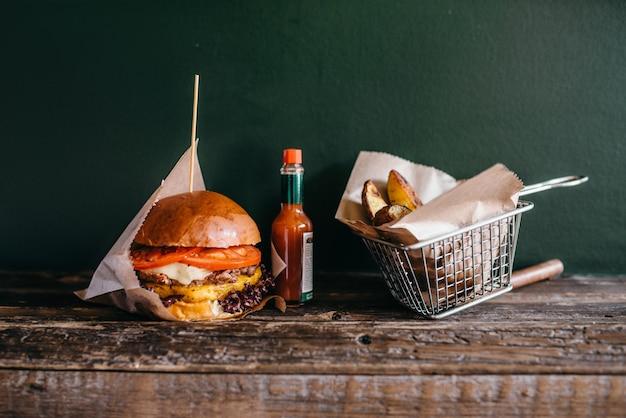 Hambúrguer fresco grelhado e batata na mesa, closeup.