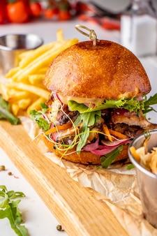 Hamburguer fresco vegetariano com cogumelos e legumes, servido com batatas fritas em uma placa de madeira, fast-food saudável, closeup