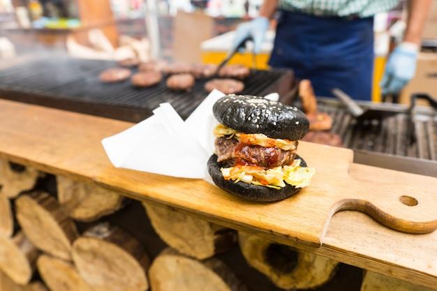 Hambúrguer gourmet servido sozinho na tábua de madeira com guardanapos na bancada da barraca de comida com uma pessoa cozinhando hambúrgueres na churrasqueira no fundo