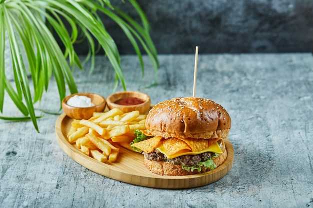 Hambúrguer grande com batata frita no prato de madeira na superfície de mármore