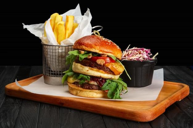 Hambúrguer grande com batatas fritas e salada de repolho
