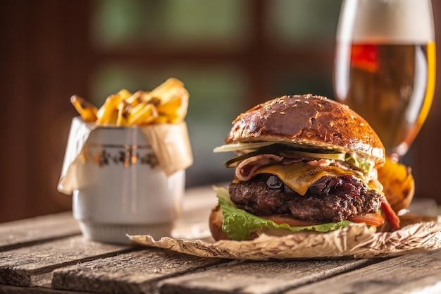 Hambúrguer grande com carne, queijo, cebola caramelizada, alface, tomate, maxixe, tudo em um pãozinho ao lado de rodelas de batata e um copo de chope.
