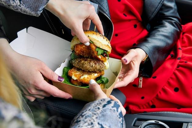 Hambúrguer grande e suculento com queijo e duas costeletas de gente olhando o recheio