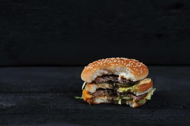 Hambúrguer mordido em um rústico escuro