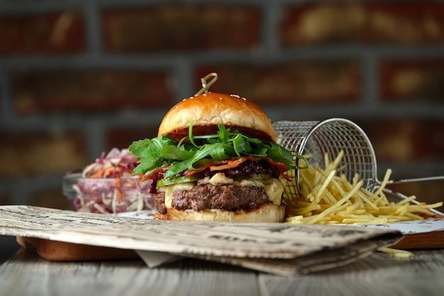 Hambúrguer na mesa de madeira com queijo, bacon, tomate, salada verde e vermelha e batata frita