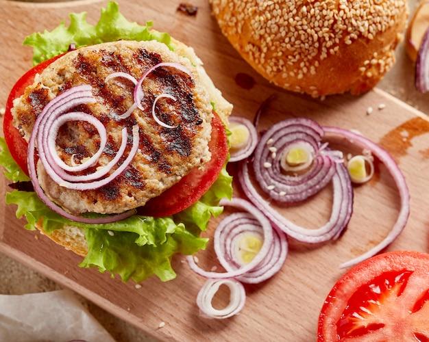 Hamburguer na placa de madeira com cebola e tomate