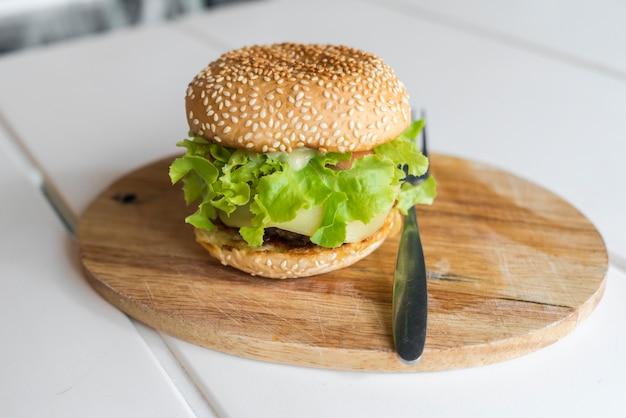 Hambúrguer na placa de madeira. conceito de fast food