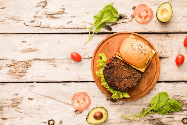 Hambúrguer na tábua de cortar com espinafre; tomates; abacate na placa de madeira