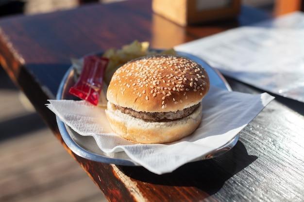 Hambúrguer no prato na mesa de madeira