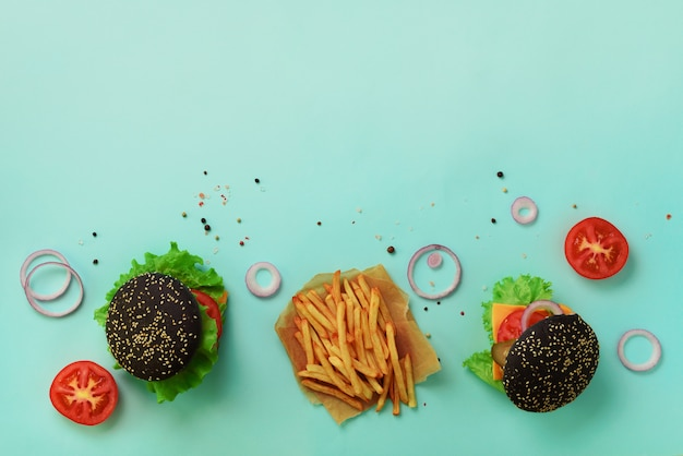 Hamburguer preto, batatas fritas, tomates, queijo, cebola, pepino e alface no fundo azul. tire a refeição. conceito de dieta insalubre