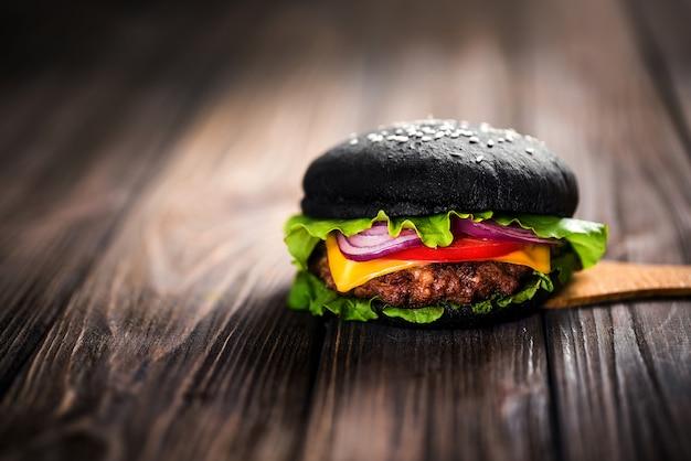 Hambúrguer preto caseiro com queijo. cheeseburger com pão preto o