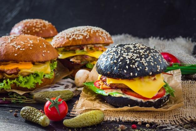 Hambúrguer preto com guisados de carne, queijo, repolho roxo e molho balsâmico, servido em uma pequena tábua de madeira sobre a mesa de madeira com fundo preto.