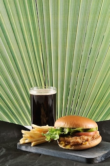 Hambúrguer redondo com costeleta de frango e batatas fritas e um copo de coca-cola