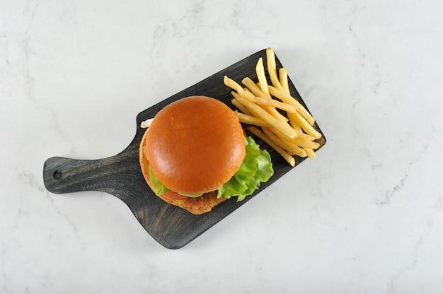 Hambúrguer redondo com costeleta de frango e batatas fritas